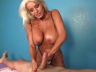 Client receives a handjob wits the big-tittied mature masseuse